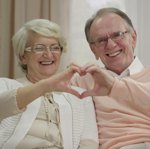 Man en vrouw gelukkig op de bank en maken een hart met hun handen