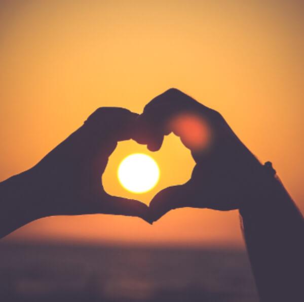 twee handen maken een hart waar de zon door schijnt: geniet van langer zelfstandig thuis wonen